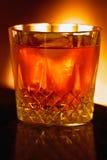 Bebida de aquecimento do fireside, backlit pela luz do incêndio Fotografia de Stock