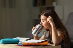 Bebida de consumición adolescente estudiosa de la energía que estudia Fotografía de archivo