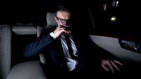 Bebida de consumición ejecutiva en el asiento trasero del coche, camino de casa después del día ocupado duro fotografía de archivo