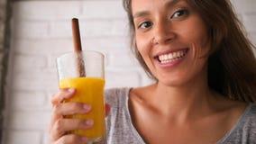 Bebida de consumición sonriente joven atractiva del Smoothie de Superfoods del mango y del vegano de la muchacha mezclada concept almacen de metraje de vídeo
