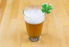 Bebida de la cerveza del día del ` s de St Patrick en un vidrio transparente con una alta espuma blanca y trébol en una base de m fotos de archivo