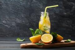 Bebida de la limonada del agua, del limón y de la menta de soda en tarro en fondo negro Imágenes de archivo libres de regalías