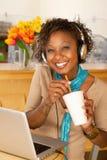 Bebida de la mujer joven y computadora portátil de consumición con Fotografía de archivo libre de regalías