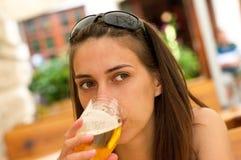 Bebida de la mujer una cerveza Foto de archivo libre de regalías