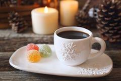 Bebida de la Navidad: café, caramelos coloridos y velas ardientes Foto de archivo