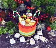 Bebida de la Navidad con el muñeco de nieve y la melcocha Foto de archivo