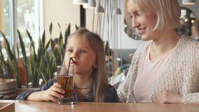Bebida de la niña un poco de bebida a través de una paja en el café fotografía de archivo libre de regalías