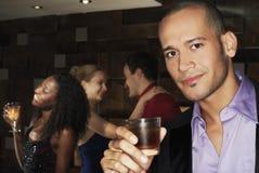 Bebida de la tenencia del hombre con la gente que baila detrás en la barra Fotografía de archivo