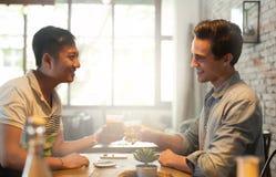Bebida de la tostada de dos alegrías de los hombres, amigos asiáticos de la raza de la mezcla Imágenes de archivo libres de regalías