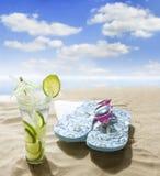 Bebida de las gafas de sol en arena en la playa Imagen de archivo libre de regalías