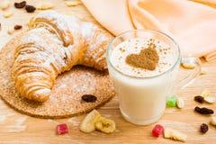 Bebida de leche con canela y el cruasán Imagen de archivo