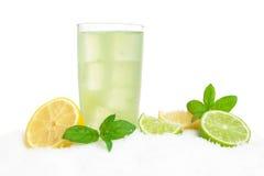 Bebida de Mojito no gelo com limões, cais, folhas no branco fotografia de stock