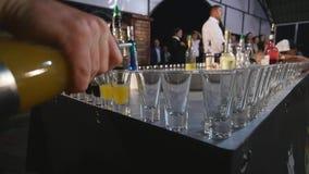 Bebida de Pouring Colorful Alcoholic del camarero en los vasos de medida primer almacen de metraje de vídeo