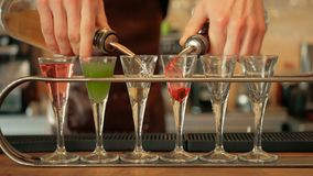 Bebida de Pouring Colorful Alcoholic del camarero en los vasos de medida primer metrajes