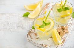 Bebida de refrescamento fria do verão com limão e hortelã no fundo de madeira imagens de stock royalty free