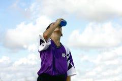 Bebida de restauración de consumición del muchacho sediento Foto de archivo libre de regalías