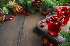 Bebida del arándano en el fondo de madera adornado con las ramas del abeto, las especias y las bayas frescas Fotos de archivo libres de regalías