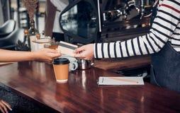 Bebida del café de la paga del cliente con la tarjeta de crédito al barista, cierre encima de h fotos de archivo