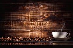 Bebida del café del fondo en una taza con los granos de café en textura de madera imagenes de archivo
