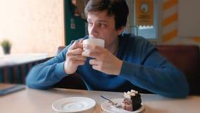 Bebida del hombre joven un té en café almacen de video
