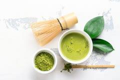 Bebida del té del matcha y accesorios verdes del té en el fondo blanco Imagen de archivo