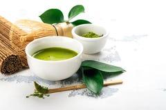 Bebida del té del matcha y accesorios verdes del té en el fondo blanco Imagen de archivo libre de regalías