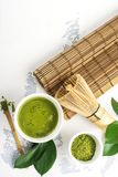 Bebida del té del matcha y accesorios verdes del té en el fondo blanco Fotografía de archivo