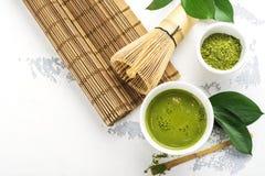 Bebida del té del matcha y accesorios verdes del té en el fondo blanco Foto de archivo