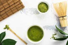 Bebida del té del matcha y accesorios verdes del té en el fondo blanco Fotos de archivo libres de regalías