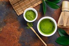 Bebida del té del matcha y accesorios verdes del té en fondo oxidado oscuro Foto de archivo