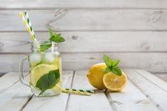 Bebida del verano, agua con el limón, hielo y menta en tarro de albañil en un fondo de madera blanco Imagen de archivo libre de regalías