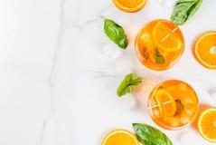 Bebida del verano con la naranja y la albahaca Fotografía de archivo