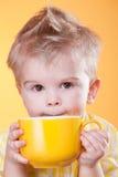 Bebida divertida del muchacho de la taza amarilla Foto de archivo libre de regalías