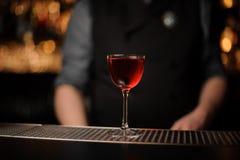 Bebida do álcool com a cereja com barman atrás fotografia de stock royalty free