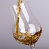 Bebida do álcool que derrama no vidro isolado Fotografia de Stock