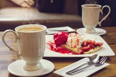 Bebida do café e crepe quentes da morango do gelado na tabela de madeira dentro Fotos de Stock
