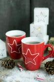 Bebida do Natal Chá ou café em umas canecas vermelhas na tabela de madeira com bastão de doces Foto de Stock Royalty Free