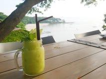 Bebida do verão: Um frasco de vidro do suco do batido da maçã está na tabela de madeira com seaview Imagens de Stock Royalty Free