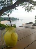 Bebida do verão: Um frasco de vidro do suco de limão congelado está na tabela de madeira com seaview Fotografia de Stock Royalty Free
