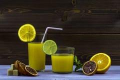 Bebida do verão Uns vidros do suco de laranja Laranja cortada, açúcar, hortelã, canela Imagens de Stock