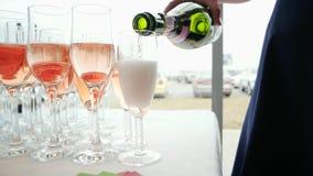 Bebida efervescente que vierte en vidrios de la botella, mano de la mujer que sostiene la botella y que vierte el champán color d almacen de video