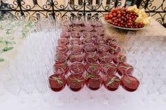 Bebida en las copas para el abastecimiento de la boda adornadas con romero Foto de archivo libre de regalías