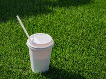 Bebida en una taza de papel con en el campo de f?tbol fotos de archivo