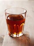 Bebida escura no vidro na tabela de madeira Fotografia de Stock Royalty Free