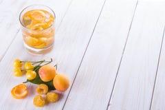 Bebida fría con los albaricoques y las frambuesas de las cerezas que se colocan en a imagen de archivo