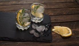A bebida fresca com limão e os alecrins na ardósia embarcam no CCB de madeira Imagem de Stock Royalty Free
