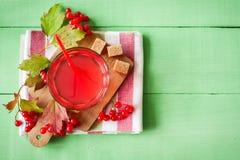 Bebida fresca del viburnum en vidrio en fondo de madera verde con las hojas y las bayas imágenes de archivo libres de regalías