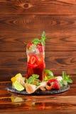 Bebida fresca do álcool do verão com morangos doces, cal suculento, hortelã, e vinho em um fundo de madeira Copie o espaço fotografia de stock royalty free