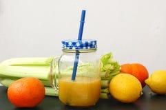 Bebida fresca saudável do batido do aipo, do limão e da tanjerina verdes no vidro com palha Imagens de Stock