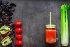 Bebida picante do tomate com aipo e pimenta Bebida do tomate no frasco cercado de legumes frescos em uma tabela de madeira Fotos de Stock
